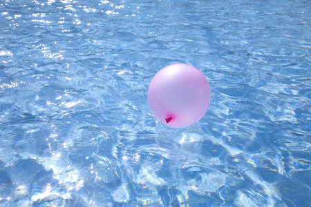 air baloon floating on blue glittering water, shallow dof photo