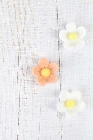 sugarcraft: three sugar blossom flowers on white old table
