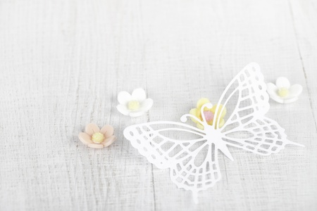 paper butterfly and three sugar blossom flowers on white old table photo