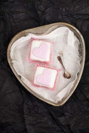 pink cupcakes in heart shaped tin,black paper background photo