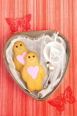 gingerbread boy and girl on tin heart shaped tray, red linen striped with butterfly backdrop photo