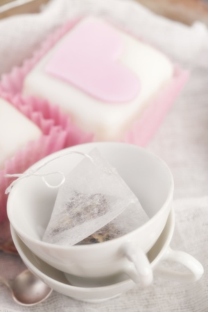 small tea cups and heart pink cupcakes, shallow dof photo