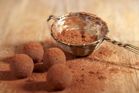 trufas de chocolate: polvo de cacao de trufas de chocolate espolvoreados y tamiz, dof superficial Foto de archivo