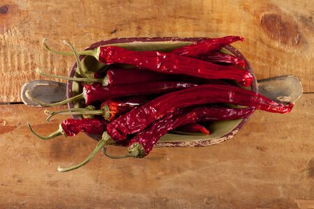 dried red hot chillies pepper in old wooden bowl, shallow dof Stock Photo - 9522837