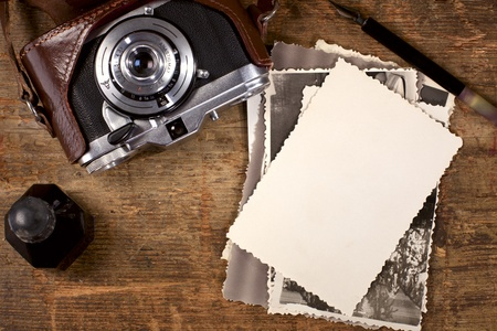 back to camera: vintage ink and  pen, old photos and camera on old wooden table Stock Photo