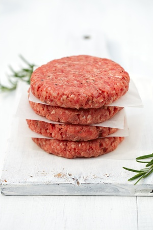 beefburger: Raw burgers for hamburgers, in a pile on white wood Stock Photo