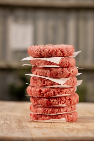 Raw burgers for hamburgers, in a pile in a garden