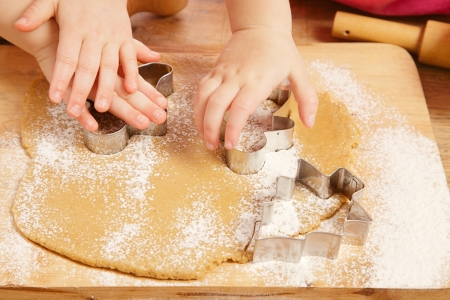 little girls cutting christmas  gingerbread cookies, hands only Stock Photo - 10443031
