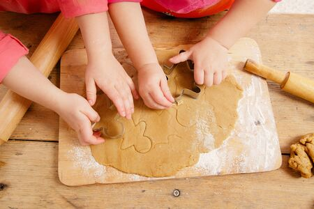 messy kitchen: little girls cutting christmas  gingerbread cookies, hands only