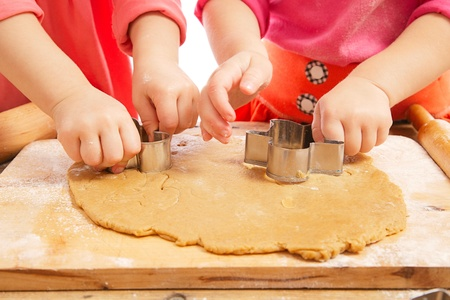 little dough: little girls cutting christmas  gingerbread cookies, hands only