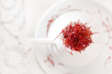 intense flavor: moroccan saffron treads in pile, on white china cup and wood, shallow dof Stock Photo