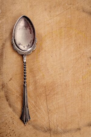 retro desset spoon  on old wooden table background photo