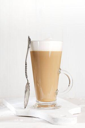 frothy: caff� latte con latte schiumoso nel bicchiere alto, stile rustico, in legno bianco Archivio Fotografico