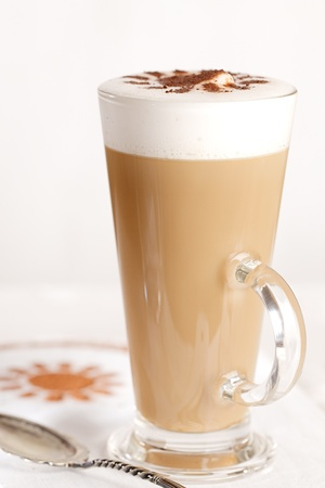 latte: coffee latte with frothy milk in tall glass, rustic style, white wood