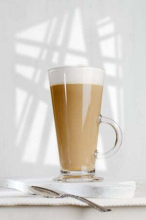 frothy: coffee latte with frothy milk in tall glass, gobo light, white wood