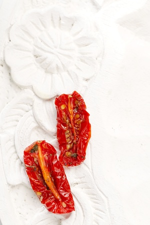 sun-dried tomatoes with olive oil in an old  white wooden background photo