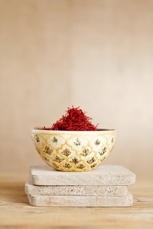 intense flavor: moroccan saffron treads in bowl, on wood, shallow dof Stock Photo