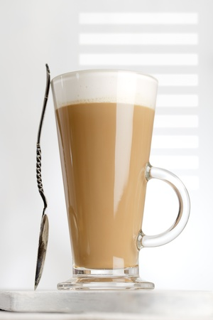 coffee latte with frothy milk in tall glass, gobo light, white wood