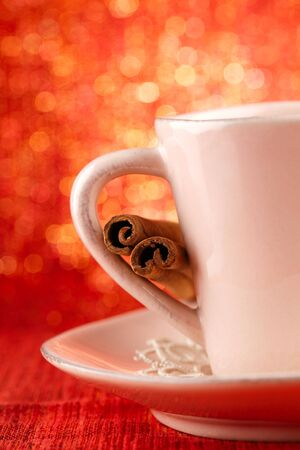 festive cup of hot xmas drink with cinnamon sticks and golden red glitter background photo