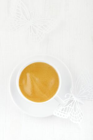 expresso: espresso coffee in white cup  and saucer, white wooden table
