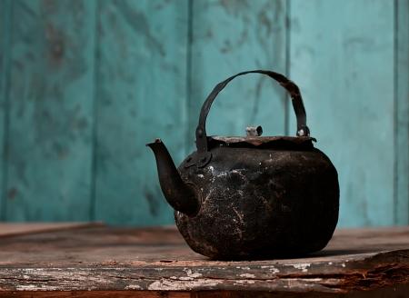 kettles: tetera tiznada de edad en la mesa de edad en la cocina