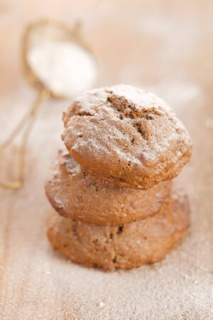 caster: soft ginger cookies three stacked and dusted on wooden table, sieve with caster sugar on background, shallow dof