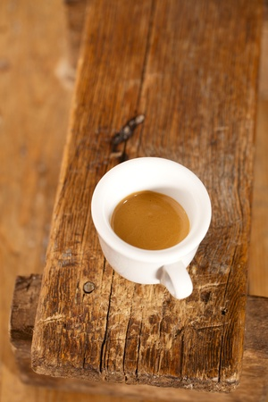 espresso coffee in thick white cup on old wooden bench photo