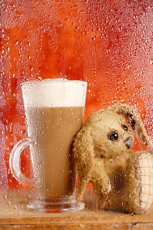 bunny and coffee latte behind rainy window, shallow dof on glass with droplets photo