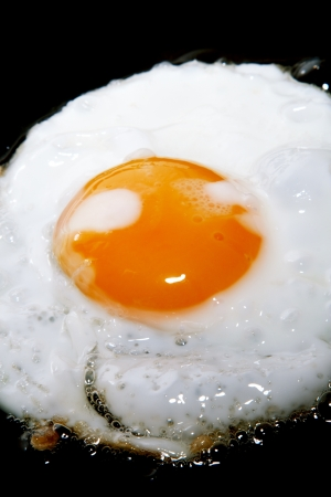 cooking frying egg with yolk on black pan photo