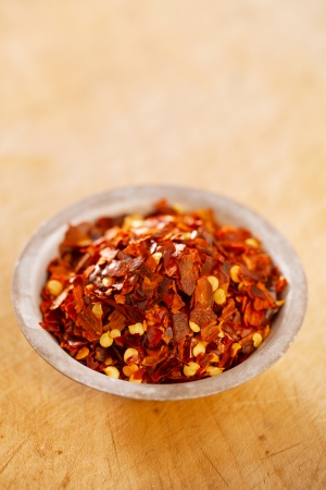 extreme heat: Hot Red Chilli Chillies pepper crushed in tin bowl on wood