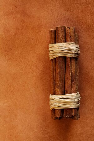 chap sticks: old weathered leather  background with cinnamon sticks stock photo image