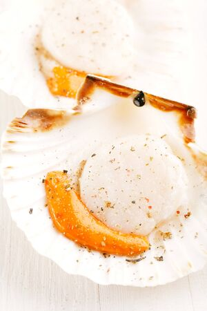 open topped: two open scallops, topped with salt and pepper, ready for grill, on white wooden backdrop