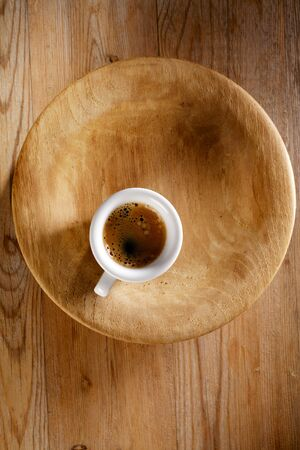 espresso coffee in thick white cup on old wooden plate photo