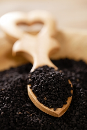 nigella seeds: black cumin or caravay or onion seeds in heart shape wooden spoon Stock Photo