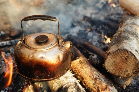 coffee pot: sooty teapot on camping bonfire