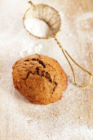 galletas de jengibre: galleta de jengibre suave en la mesa de madera, tamiz con azúcar en polvo en el fondo, dof bajo