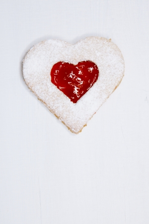 linzer homemade cookie with heart shape raspberry jam window, on white wooden backdrop photo