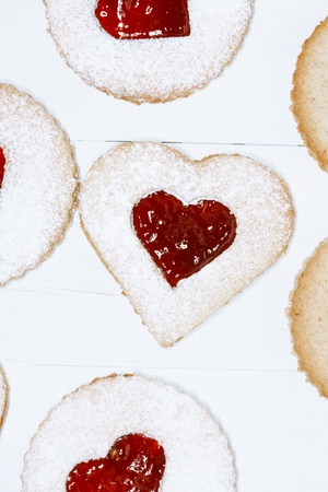 linzer homemade cookies with heart shape raspberry jam window, on white wooden backdrop photo
