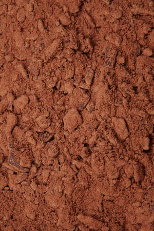 chocolate background: cocoa powder with small pieces of chocolate on background , shallow DOF