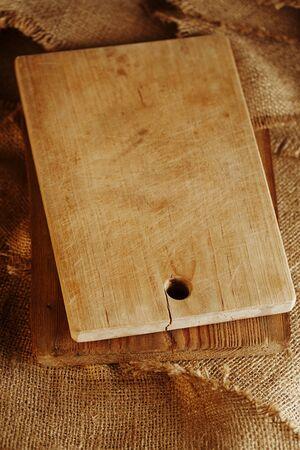cutting bord: old woden choppig board on hessian backdrop, shallow dof