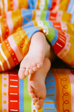 toddlers girl  feet in a bed under the morning sun, shallow DOF Banco de Imagens