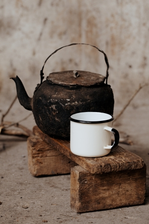 sooty: sooty old teapot and white enamel mug on small wooden bench Stock Photo