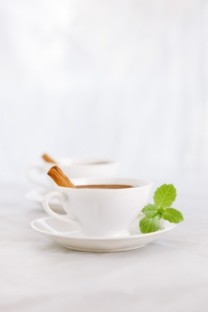 hot chocolate in white cups with cinnamon sticks and mint leaves, sunlight spots, shallow DOF Stock Photo - 16810215