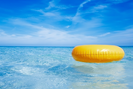 beach toys: floating yellow ring on crystal blue sea water with sky, shallow dof