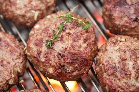 bbq background: food meat - burgers on bbq  barbecue grill with fire  Shallow dof  Stock Photo