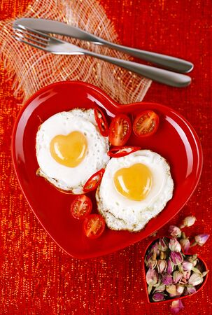 yellow heart: fried egg with heart shape yolks on red plate,  setting for lovely breakfast, glitter background,