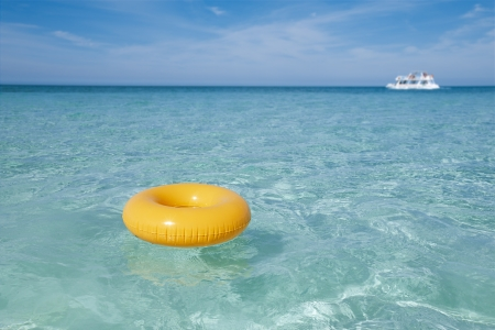 float tube: floating ring on blue clear sea with white boat, shallow dof
