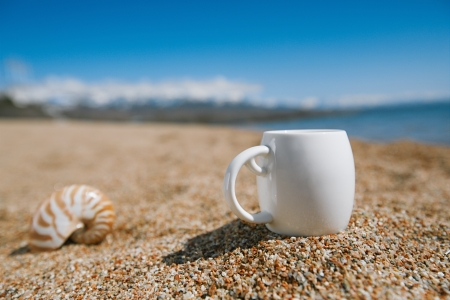 issyk kul: espresso coffee cup  on the issyk-kul beach sand with mountains on background