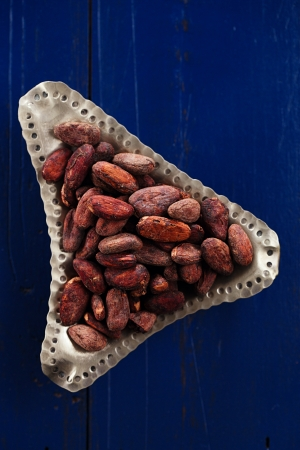 roasted cocoa chocolate beans on dark blue wood background photo