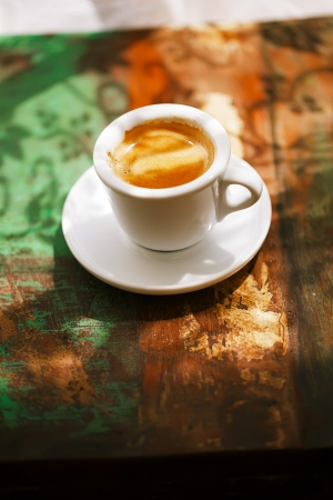 espresso coffee cup on rustic table with sun photo